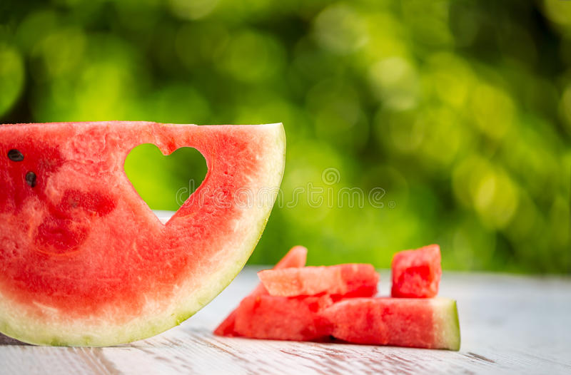 Watermelon slice with heart shape hole. Concept summer love stock photo