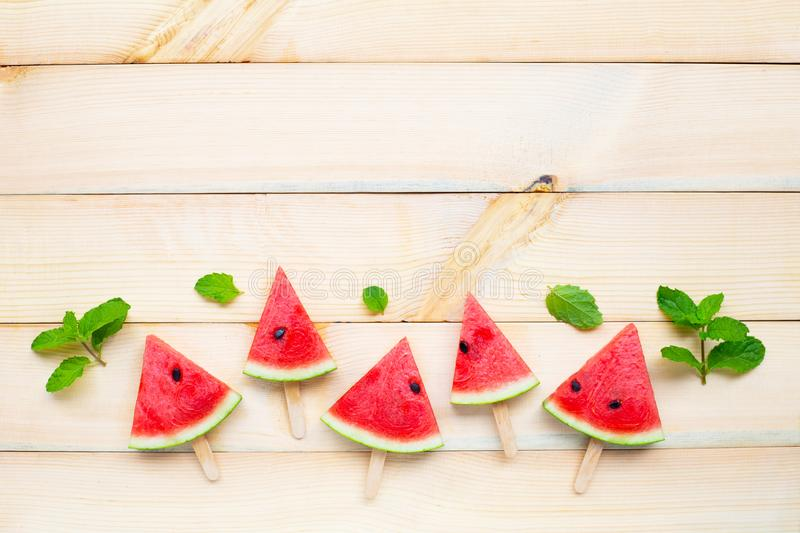 Watermelon slice popsicles on brown wooden background stock photos
