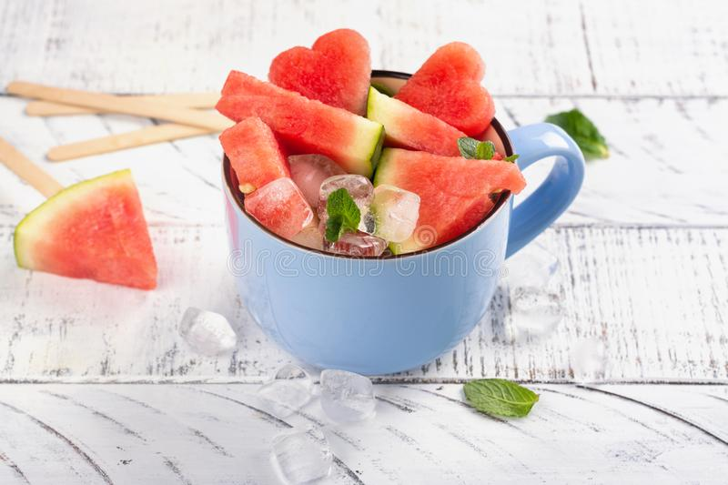 Watermelon slices in a blue porcelain cup on white wooden table. Making water melon popsicles, summer fruit dessert. Copy space stock photo