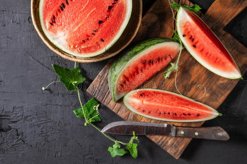Watermelon slices cut in half on a wooden cutting board stock photos