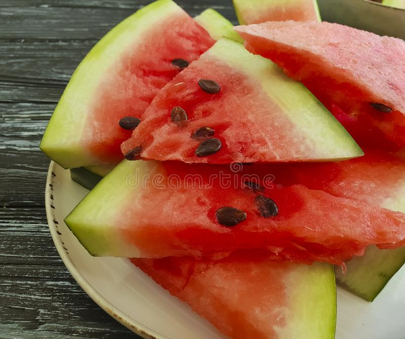 Watermelon slices detox natural delicious on a black wooden rustic background. Watermelon slices on a black wooden background nutrition detox summer rustic royalty free stock images