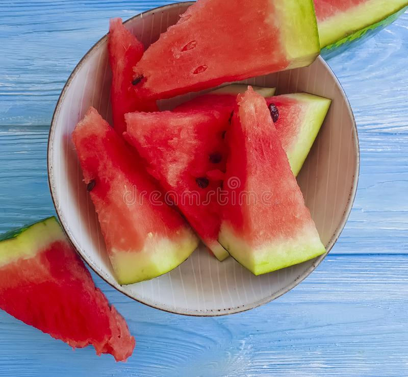 Watermelon slices natural, plate organic summertime on a blue wooden background. Watermelon slices plate on a blue wooden background summertime natural organic stock image