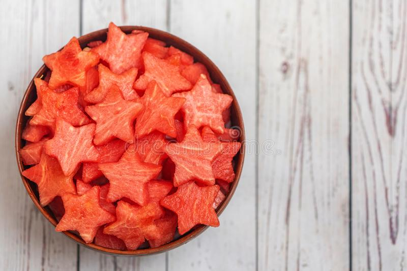 Watermelon slices in the shape of a star in bowl on a light wooden background. Top view, with copy space stock photography