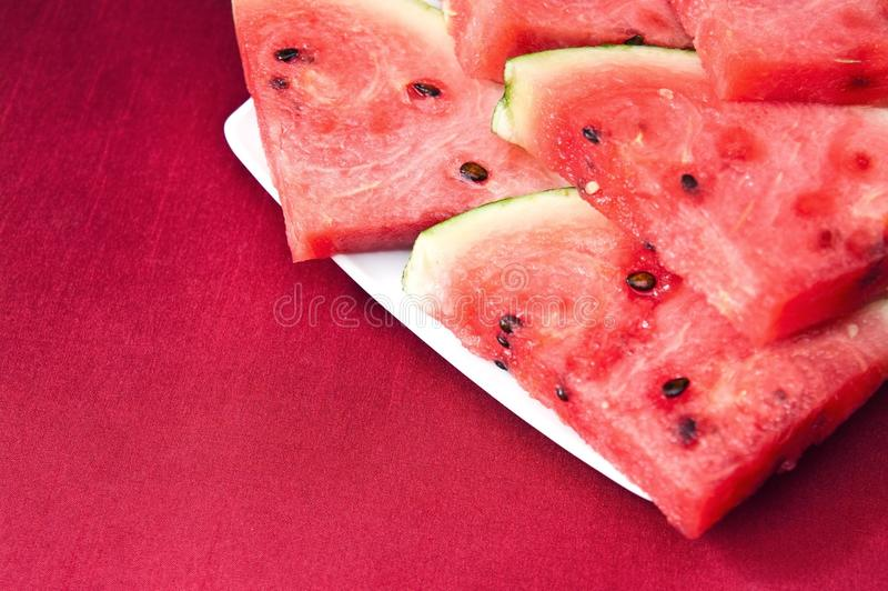 Watermelon slices. Still life of red watermelon slices on a plate and red tablecloth stock photography