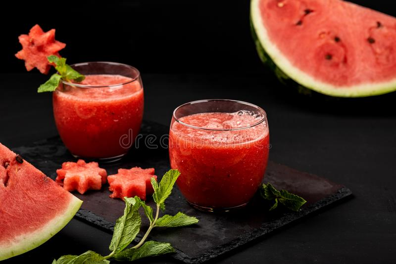 Watermelon smoothie fresh juice with mint and pieces in the shape of stars on a black background. Summer healthy drinks. royalty free stock photo