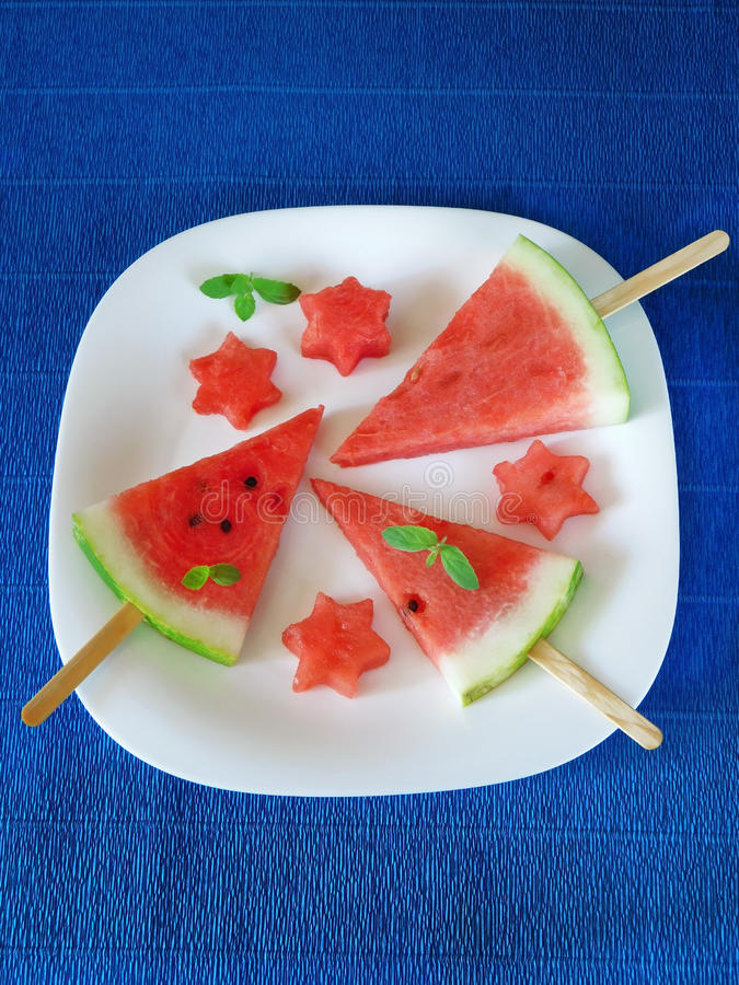 Watermelon. Watermelon pieces formed as popsicles and as stars on a white plate stock images