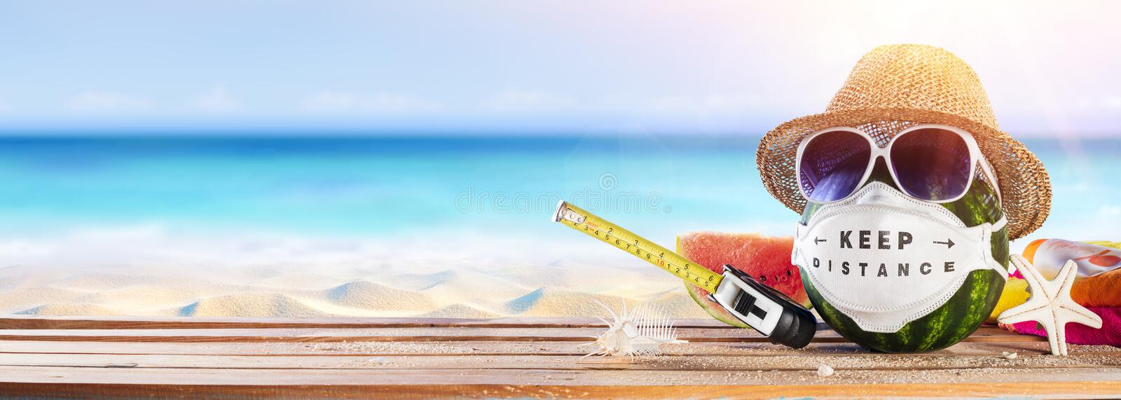 Watermelon Wearing Protective Mask - Keep Social Distance During COVID-19 Pandemic In Beach royalty free stock images