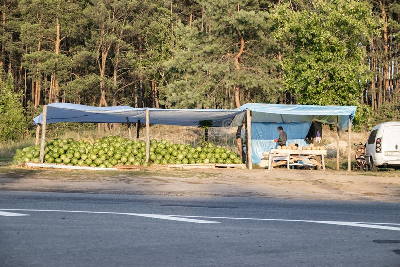 Watermelons and melons in a spontaneous market. On the side of the road, black sellers sell oriental sweets without a license to sell and without a guarantee of royalty free stock images