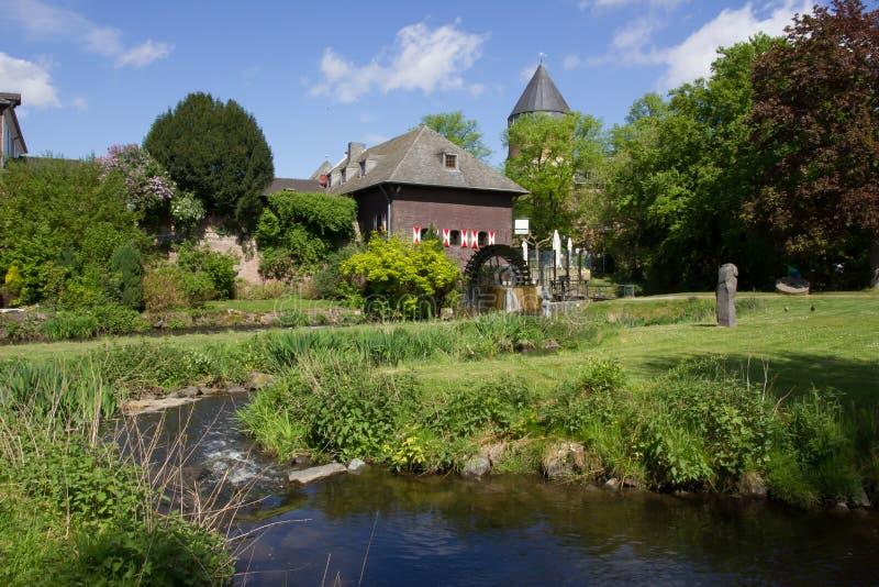 watermill en kasteel met rivier stock afbeeldingen