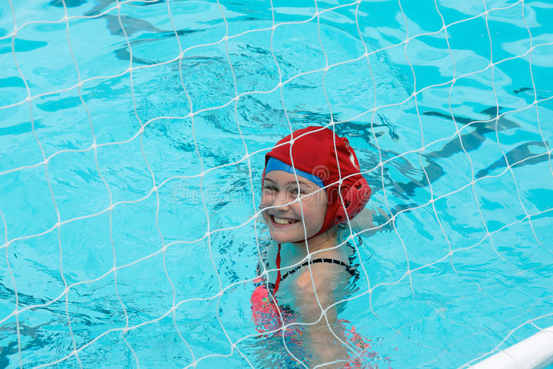 Waterpolo goalie. Young girl behind the net in a swimming pool. She is the goalie of a water polo match royalty free stock photography