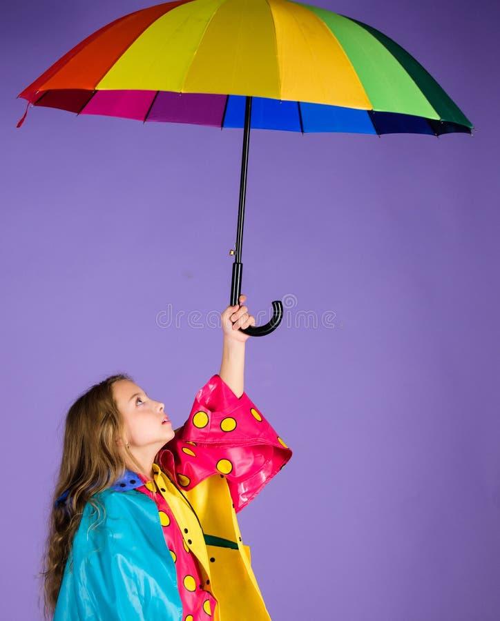 Waterproof accessories for children. Kid girl happy hold colorful umbrella wear waterproof cloak. Enjoy rainy weather. With proper garments. Waterproof stock photography