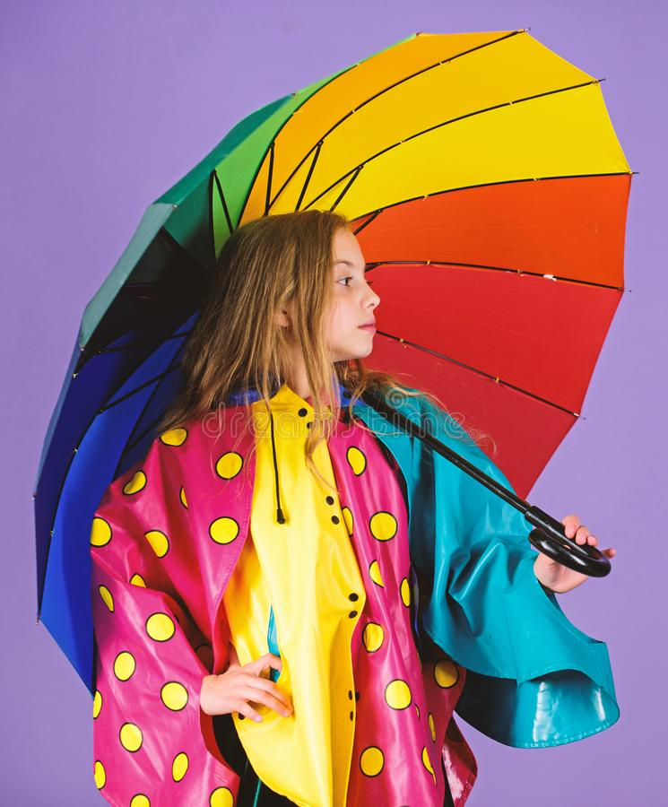 Waterproof accessories make rainy day cheerful and pleasant. Kid girl happy hold colorful umbrella wear waterproof cloak royalty free stock images