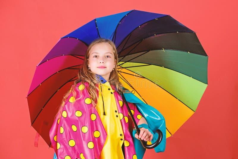 Waterproof accessories make rainy day cheerful and pleasant. Kid girl happy hold colorful umbrella wear waterproof cloak stock photo