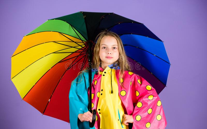 Waterproof accessories make rainy day cheerful and pleasant. Kid girl happy hold colorful umbrella wear waterproof cloak. Waterproof accessories for children stock photo