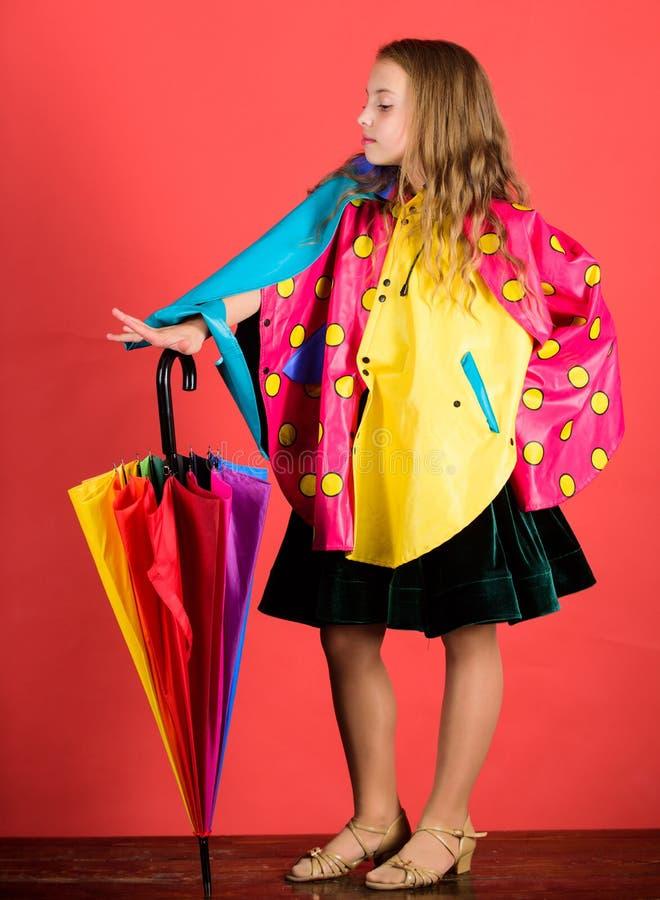 Waterproof accessories manufacture. Kid girl happy hold colorful umbrella wear waterproof cloak. Enjoy rainy weather. With proper garments. Waterproof royalty free stock images