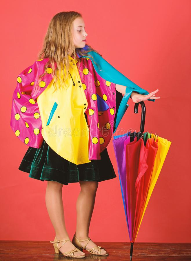 Waterproof accessories manufacture. Kid girl happy hold colorful umbrella wear waterproof cloak. Enjoy rainy weather stock photos