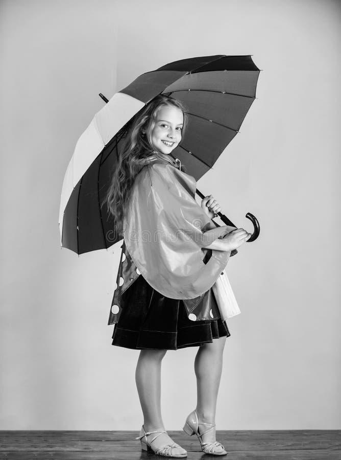 Waterproof accessories manufacture. Kid girl happy hold colorful umbrella wear waterproof cloak. Waterproof accessories. Make rainy day cheerful and pleasant stock photo