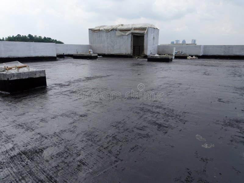 Waterproofing błona stosował pracownikami budowlanymi na górze betonowej płyty fotografia stock