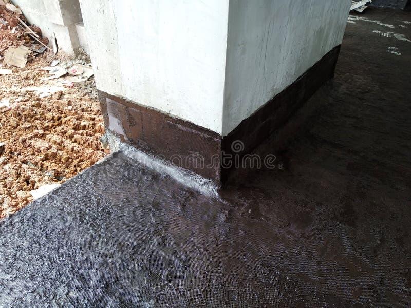Waterproofing błona stosował pracownikami budowlanymi na górze betonowej płyty zdjęcie royalty free