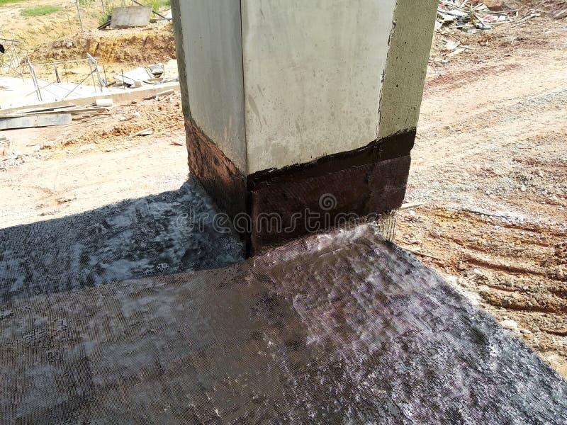 Waterproofing błona stosował pracownikami budowlanymi na górze betonowej płyty zdjęcia royalty free