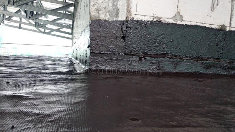 Waterproofing błona stosował pracownikami budowlanymi na górze betonowej płyty zdjęcia stock