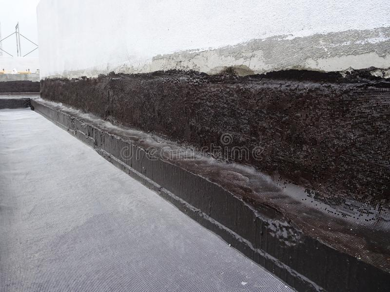 Waterproofing membrane applied by construction workers on top of the concrete slab. KUALA LUMPUR, MALAYSIA -JULY 25, 2018: Waterproofing membrane applied by royalty free stock photos