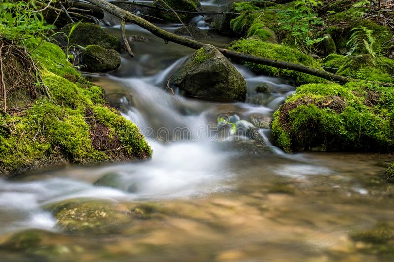 Water Tumbling Between The Moss Covered Rocks stock images