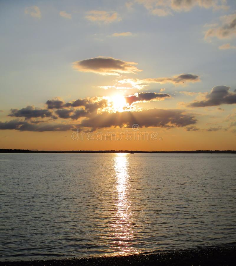 Waterscape: Sun que pendura baixo no céu que incandesce através do mar fotos de stock royalty free