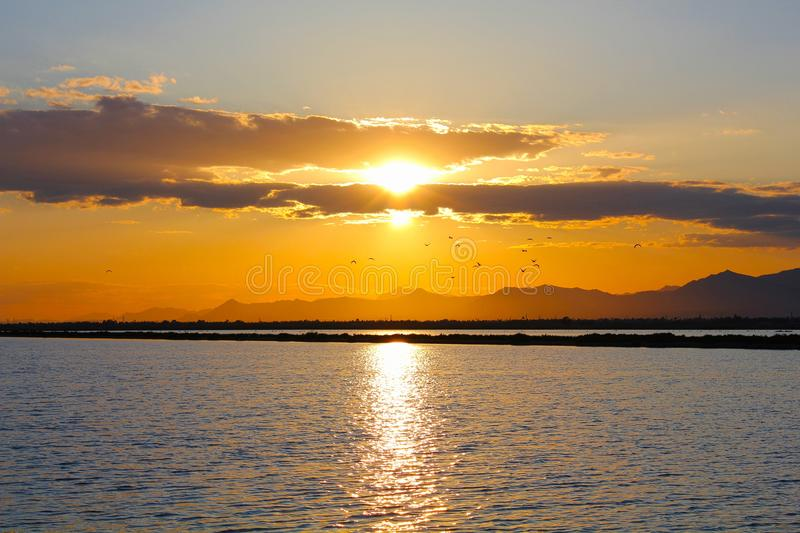 Waterscape Sunset. With a mountain background royalty free stock image