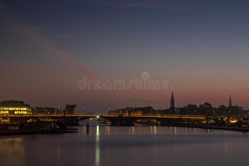 Waterside buildings in Copenhangen during a colorful sunrise ref. Lecting in the water channel royalty free stock photos