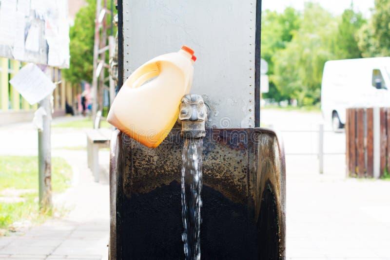 Waterspon op een stromende artesische bron Twee plastic korfflessen stock afbeelding