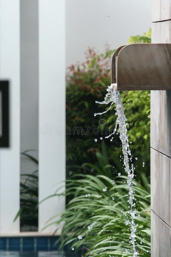 Waterstraal die in het zwembad vallen Zwembad dat van palmen in de yard van villa wordt omringd stock foto