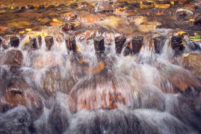 Waterstroom van rivier in regenwoudoverstroming door houten waterkering en rotsen royalty-vrije stock foto