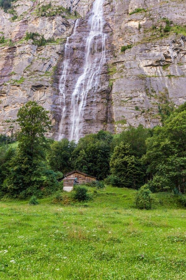 Waterval en plattelandshuisje in Jungfrau-vallei in Lauterbrunnen, Zwitserland royalty-vrije stock foto