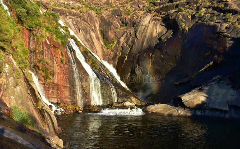 Waterval met regenboog Rode rotsen, vegetatie, waterbezinningen en zonsonderganglicht met schaduwen Ezaro, Galicië, Spanje stock foto's