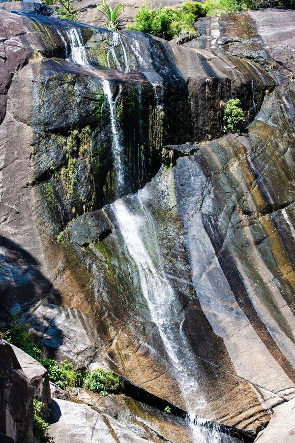 Waterval in rotsachtige bergen in regenwoud op tropisch eiland stock fotografie