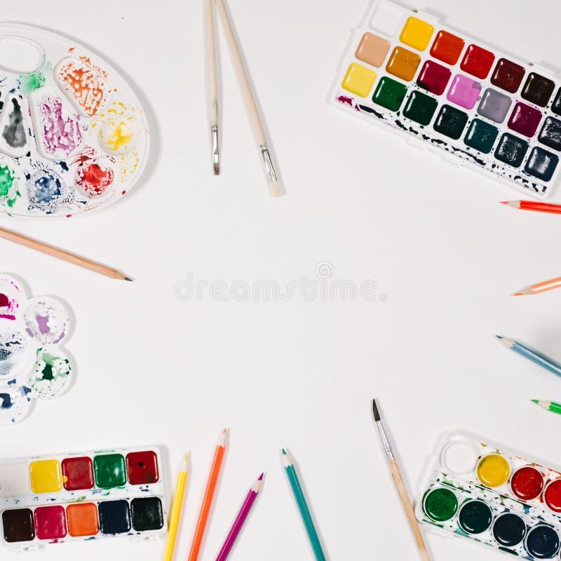 Waterverf, kleurenpotloden, palet en borstels bij witte achtergrond Vlak leg, hoogste mening stock afbeeldingen