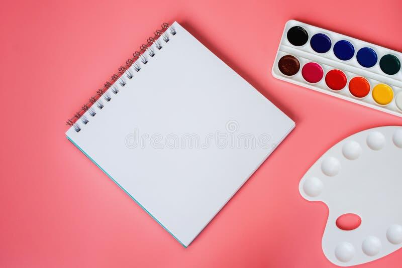 Waterverf, pallet en sketchbook met een blanco pagina op roze achtergrond stock afbeelding