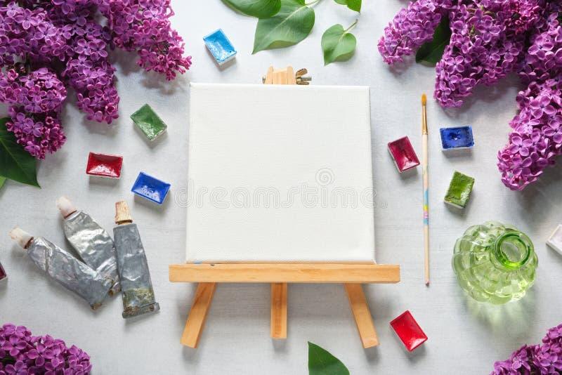 Waterverfverven, borstel voor het schilderen, verfbuizen, leeg canvas op schildersezel, waterverfverven en lilac bloemen stock afbeelding