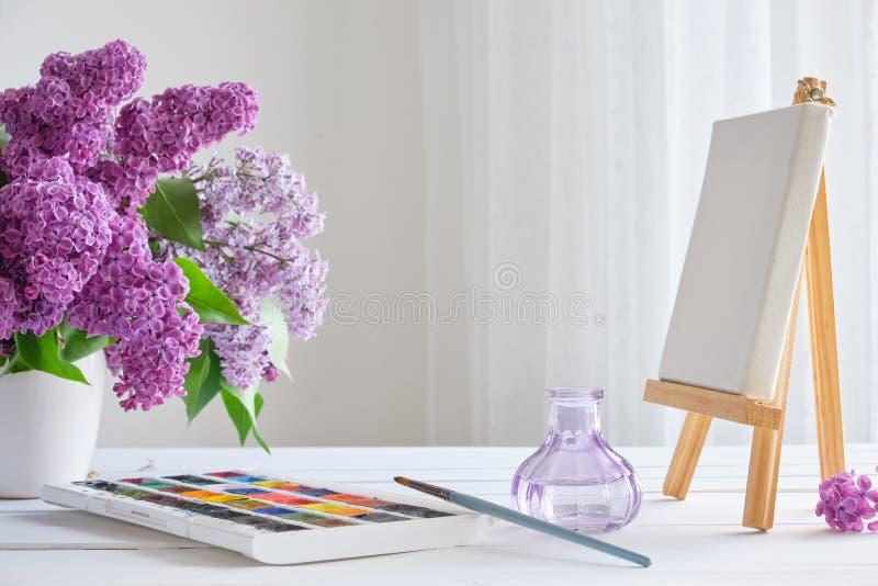 Waterverfverven, canvas op schildersezel en lilac bloemenboeket op lijst royalty-vrije stock afbeelding