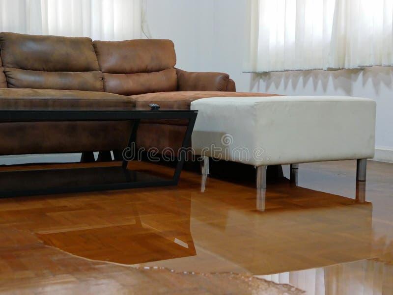 Waterverspreiding / overstroming op de vloer van het woonkamerparket in een huis - schade veroorzaakt door waterlekkage stock afbeelding