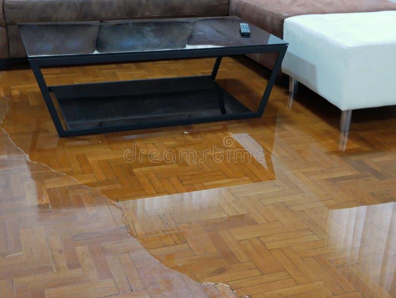Waterverspreiding / overstroming op de vloer van het woonkamerparket in een huis - schade veroorzaakt door waterlekkage stock fotografie