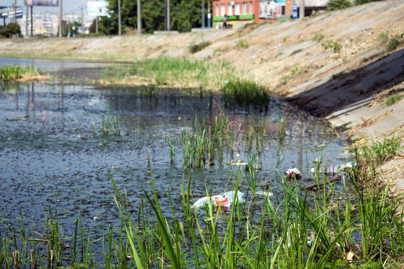Watervervuiling milieu Groen plastic flessen en huisvuil stock fotografie