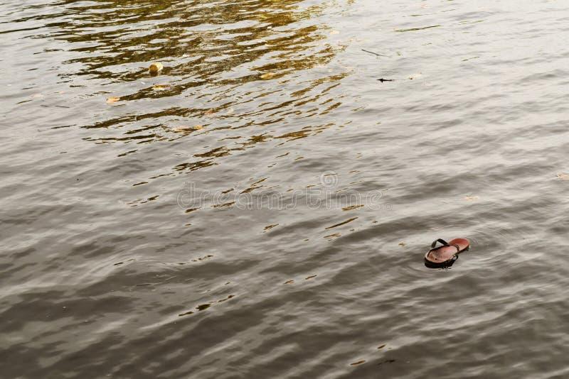 Watervervuiling: pantoffels die bij een rivier drijven royalty-vrije stock foto's
