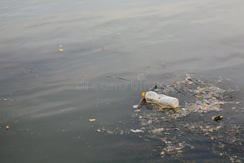 Watervervuiling - plastic fles op rivieroppervlakte royalty-vrije stock afbeeldingen