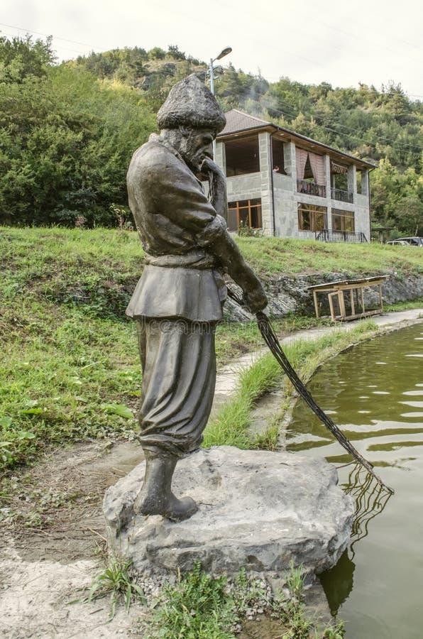 Watervijver met beeldhouwwerkvisser met verlaten netto, op de rivier Aghstev, dichtbij de restaurant` Gouden vissen ` dichtbij de stock fotografie