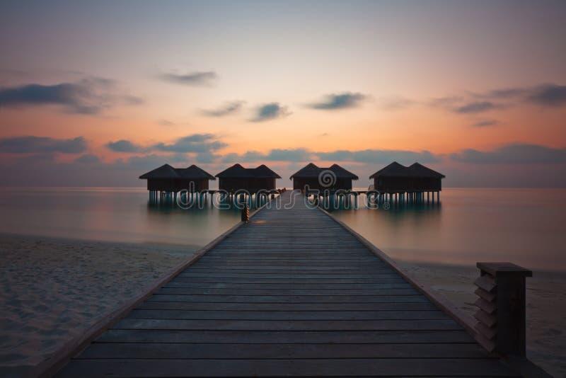 Watervilla au coucher du soleil image stock