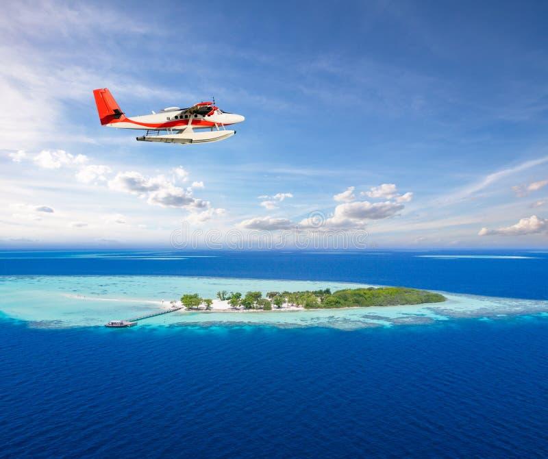 Watervliegtuig die boven klein tropisch eiland op de Maldiven vliegen stock foto