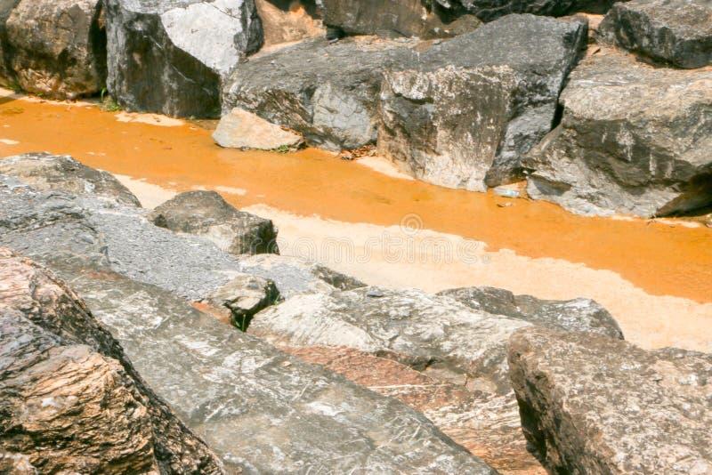 Brown arid waterway and large boulders stock image