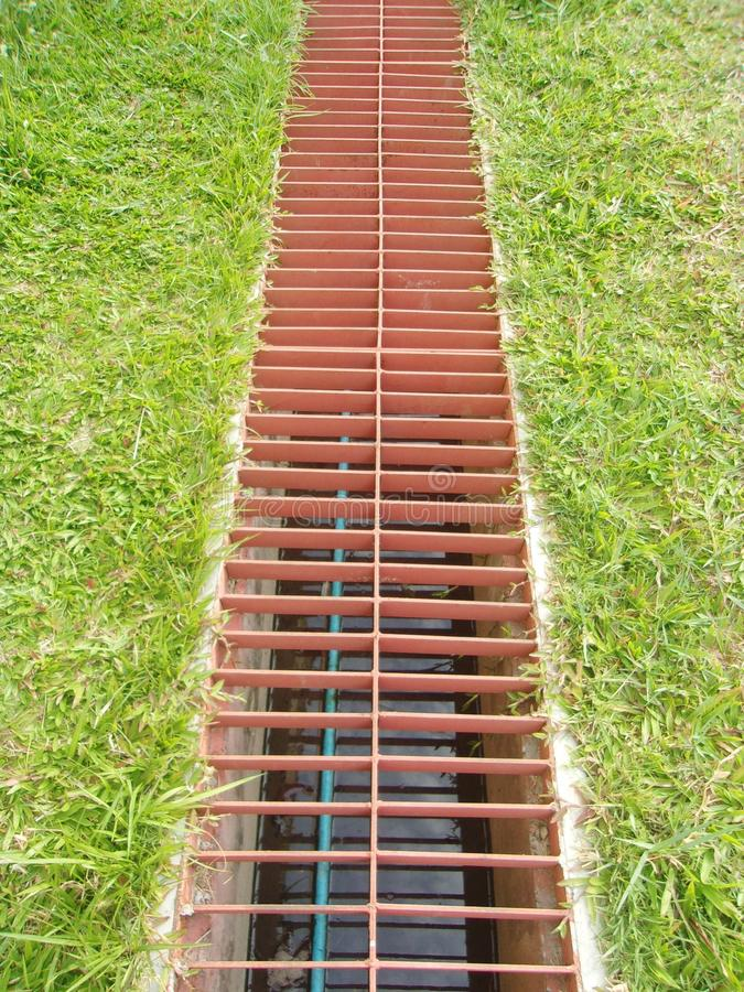 Waterway and grass. iron grate of water drain in grass garden field. Waterway and grass. iron grate of water drain in grass garden field or backyard royalty free stock photography
